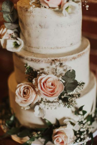 Semi-naked cake with pink rose decor on tree stump stand for rustic wedding