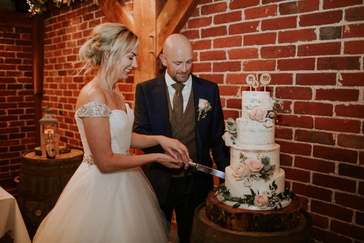 Bride and groom cut the semi-naked wedding cake at Bride and groom at The Ferry House Inn