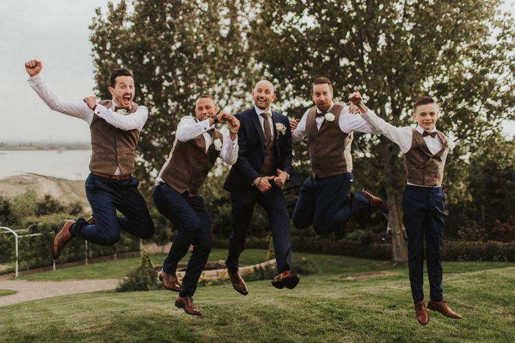 Groom and his groomsmen at outdoor wedding wearing brown waistcoats and navy blue trousers