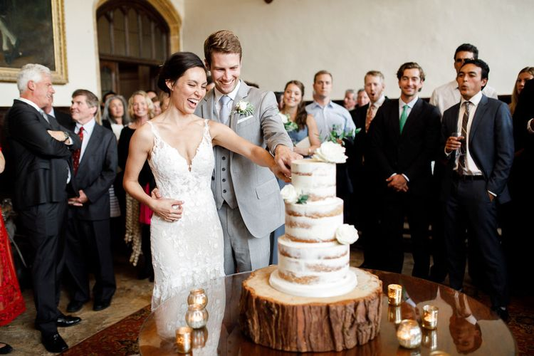 Bride and Groom Cut The Wedding Cake At Wedding With Blue Bridesmaid Dresses