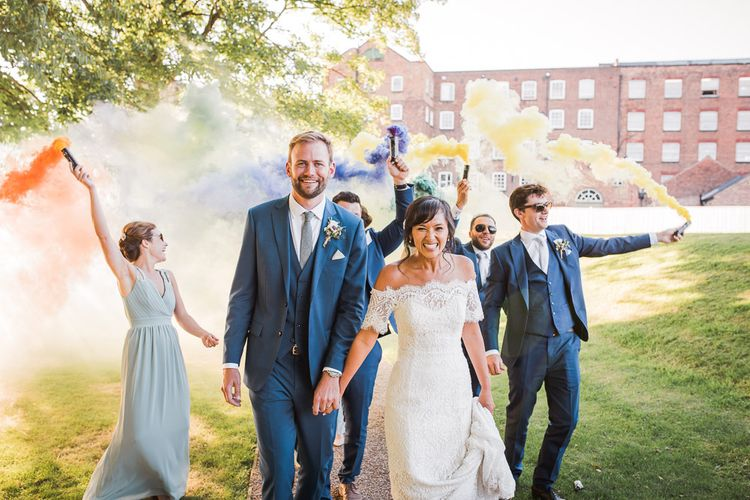 Wedding Party with Colourful Smoke Bombs | Bride in Lace Watters Dress with Bardot Neckline and Buttons Down Back | Bridal Up Do | Groom in Royal Blue Three-Piece Suit from Moss Bros. with Silver Tie and Pocket Square from T.M.Lewin | Bridesmaids in Sage Green Dresses with Embellished Straps from ASOS |  Smoke Bombs and Chinese Paper Fans Backdrop with Bride in Bardot Dress | Twig & Vine Photography