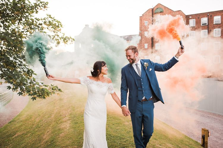 Bride and Groom with Colourful Smoke Bombs | Bride in Lace Watters Dress with Bardot Neckline and Buttons Down Back | Bridal Up Do | Groom in Royal Blue Three-Piece Suit from Moss Bros. with Silver Tie and Pocket Square from T.M.Lewin | Smoke Bombs and Chinese Paper Fans Backdrop with Bride in Bardot Dress | Twig & Vine Photography