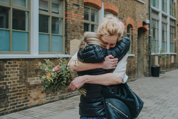 Wedding Guest Hugs | Bride in Wrap Front Wedding Dress | Coral Peony Humanist Wedding at The Tab Centre Shoreditch | Remain in the Light Photography