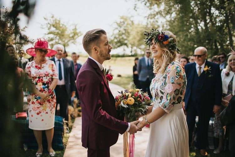 Outdoor Wedding Ceremony with Bride in Colourful Embroidered Luna Bride Wedding Dress and Groom in Burgundy Paul Smith Suit