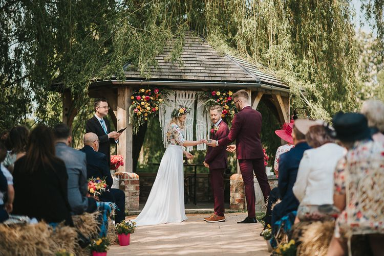 Outdoor Wedding Ceremony with Bride in Colourful Embroidered Luna Bride Wedding Dress and Groom in Burgundy Paul Smith Suit Exchanging Rings