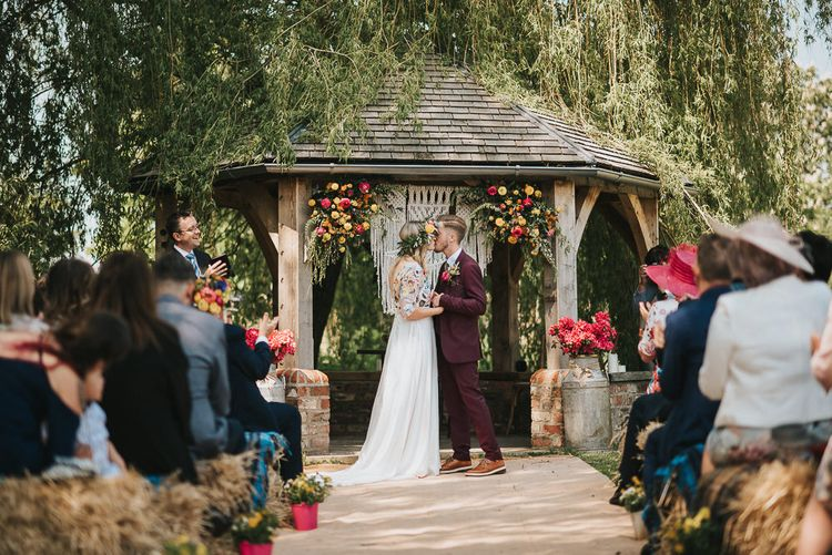 Outdoor Wedding Ceremony with Bride in Colourful Embroidered Luna Bride Wedding Dress and Groom in Burgundy Paul Smith Suit Standing in Front of Macrame and Flower Decorated Altar
