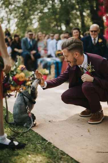 Groom in Burgundy Paul Smith Suit Giving Pet Dog a High Five