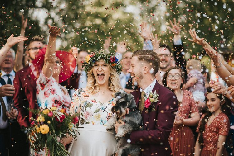 Confetti Moment with Bride in Colourful Embroidered Wedding Dress and Groom in Burgundy Paul Smith