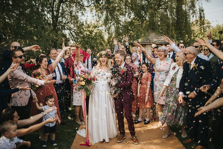 Confetti Exit with Bride in Colourful Embroidered Wedding Dress and Groom in Burgundy Paul Smith