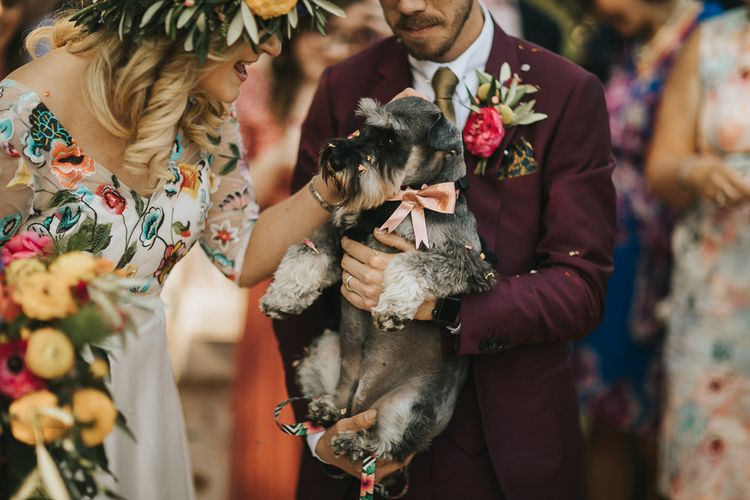 Bride and Groom Holding Pet Dog with Pink Ribbon Collar