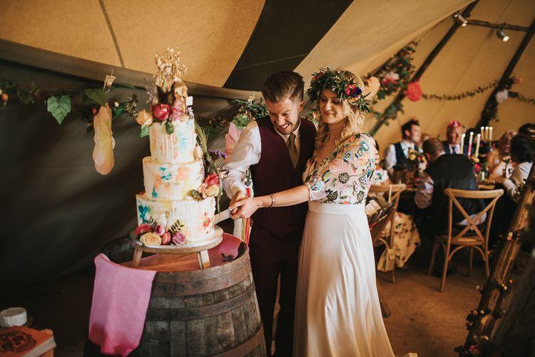 Bride and Groom Cutting Drip wedding Cake on Barrel Cake Stand