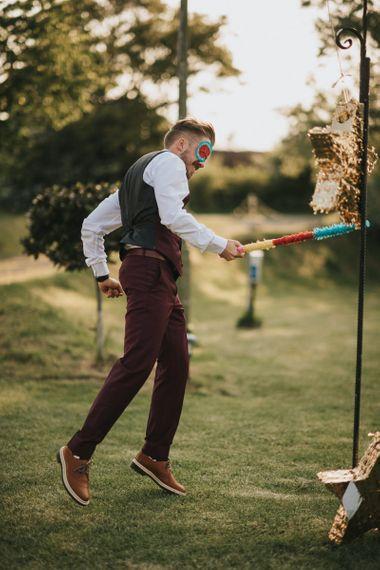 Groom in Burgundy Paul Smith Trousers and Waistcoat Hitting Gold Star Piñata