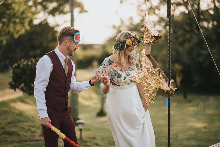 Bride in Colourful Embroidered Luna Bride Wedding Dress and Groom in Burgundy Paul Smith Suit Hitting Gold Star Piñata