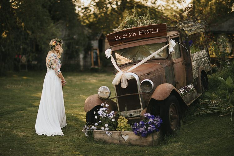 Bride in Colourful Embroidered Luna Bride Wedding Dress Standing Next to Vintage Wedding Car