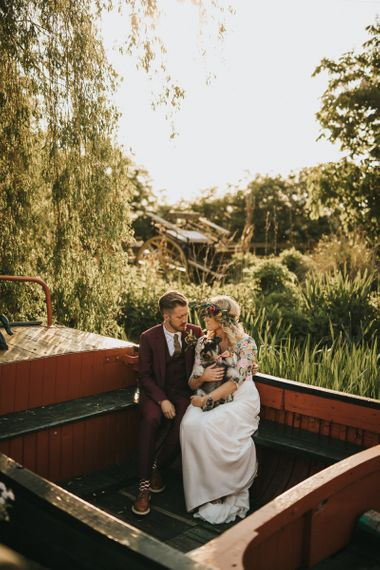 Bride in Colourful Embroidered Luna Bride Wedding Dress and Groom in Burgundy Paul Smith Suit Holding Pet Dog on a Boat