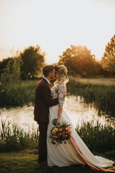 Golden Hour Portrait with Bride in Colourful Embroidered Luna Bride Wedding Dress and Groom in Burgundy Paul Smith Suit