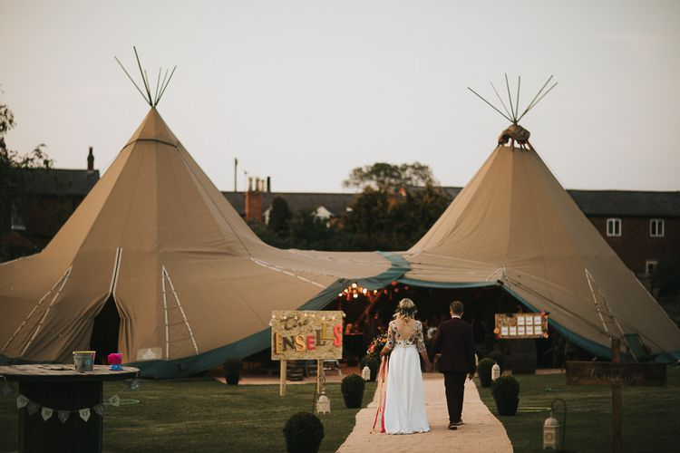 Bride in Colourful Embroidered Luna Bride Wedding Dress and Groom in Burgundy Paul Smith Suit Entering PapaKata Wedding Tipi Reception