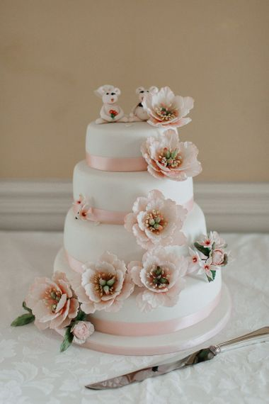 White Wedding Cake with Floral Decor and Cute Cake Toppers
