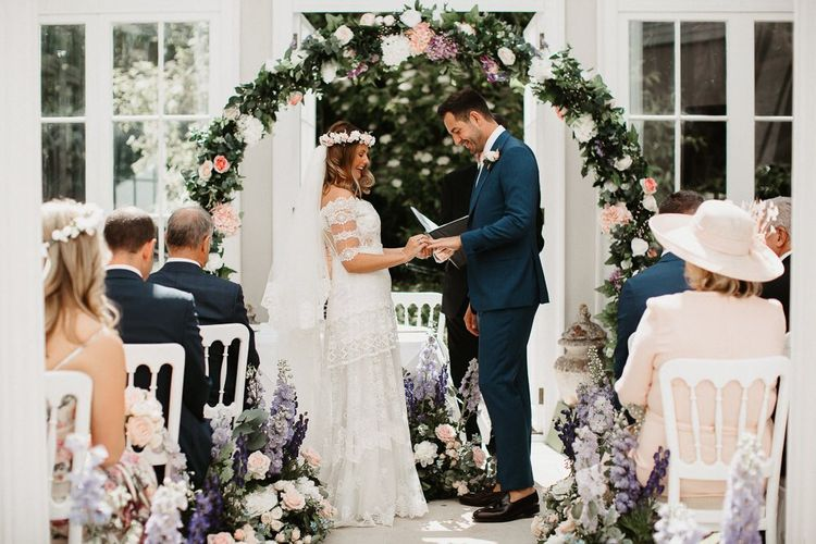 Bride and Groom Exchanging Vows Under Homemade Flower Arch