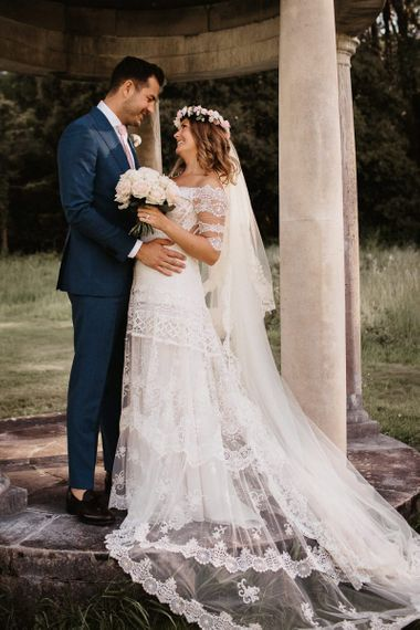 Bride and Groom In Lace Dress with Blush Bouquet and Groom in Grey Suit and Pink Tie