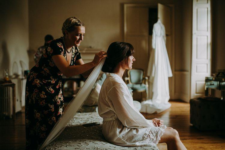 Wedding Morning Bridal Preparations with Bride in Getting Ready Robe Putting on Wedding Veil