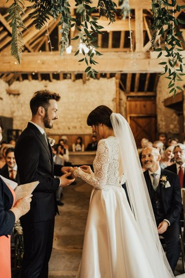 Bride in Emma Beaumont Wedding Dress and Groom Exchanging Rings at their Rustic Wedding Ceremony