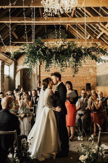 Bride in Emma Beaumont Wedding Dress and Groom in Reiss Suit Kissing Under a Hanging Floral Installation