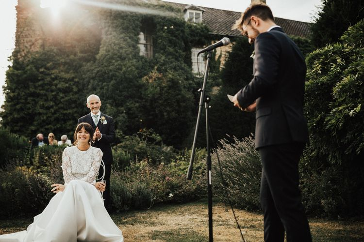 Laughing Bride in Emma Beaumont Wedding Dress as Groom Gives his Wedding Speech Outside