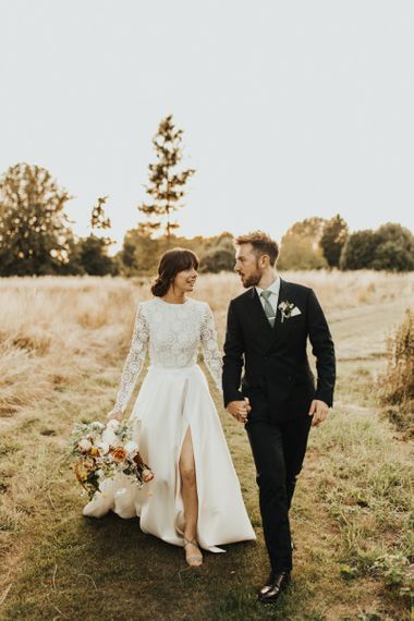 Bride in Emma Beaumont Wedding Dress with Front Slit and Groom in Reiss Suit Walking Through Fields