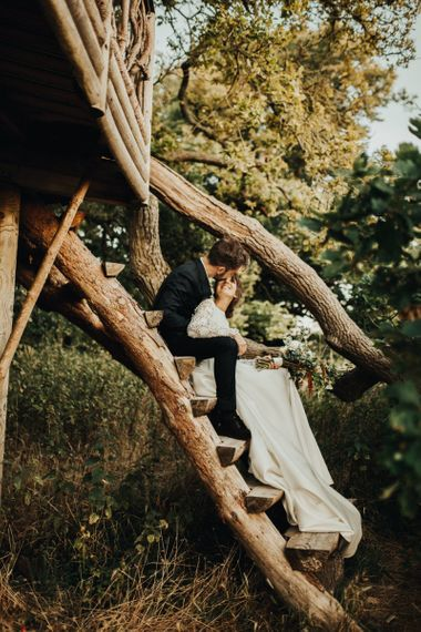 Bride in Emma Beaumont Wedding Dress and Groom in Reiss Suit Sitting Up a Tree House