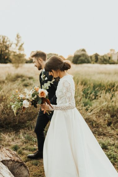 Bride in Emma Beaumont Wedding Dress and Groom in Reiss Suit Walking Through The Countryside