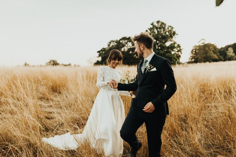 Bride in Emma Beaumont Wedding Dress and Groom in Reiss Suit Walking Through The Fields