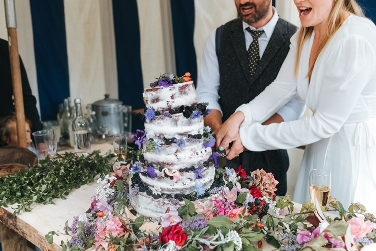 Cutting The Cake | Semi Naked Cake with Fruit | Bride in Reformation Gown | Groom In Tweed Suit | Outdoor Woodland Wedding at Wiveton Hall, Norfolk with Folk Festival Vibes | Miss Gen Photography