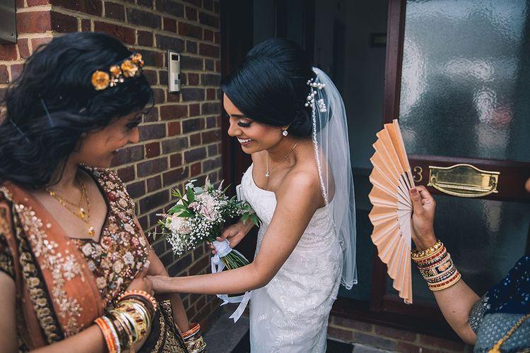 Bride in strapless wedding dress being fanned
