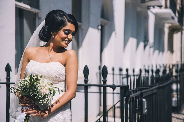Beautiful bride in strapless wedding dress with chic bridal updo at July 2020 wedding