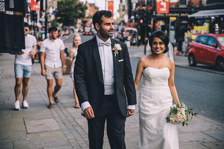 Bride in strapless wedding dress and groom in tuxedo walking around Camden Town at July 2020 wedding