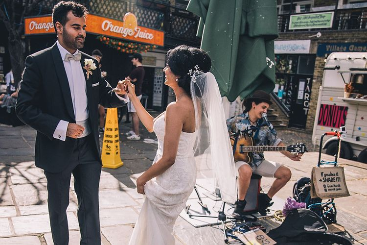 Bride and groom dancing in the street to a busker at July 2020 wedding