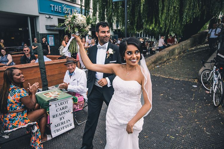 Bride and groom waving to adoring crowds in Camden Town