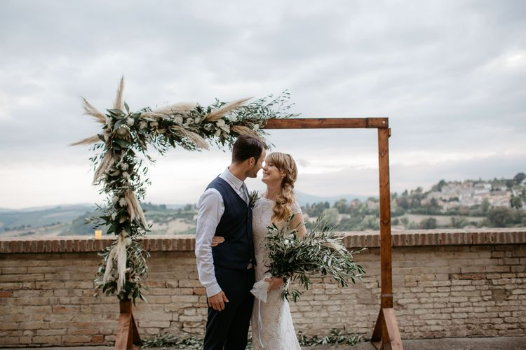 Bride with side ponytail at outdoor wedding with pampas grass decor