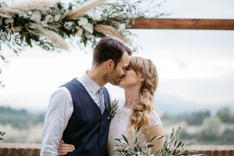Bride with side ponytail kisses new husband