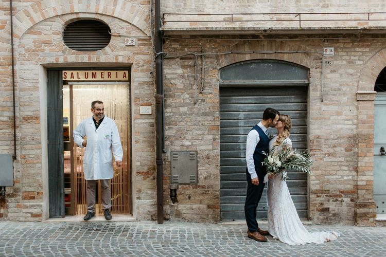Bride and groom kiss on the streets of Italy at destination wedding
