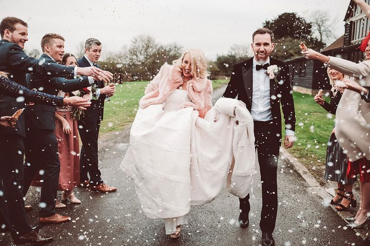Confetti Exit | Bride in Organza Justin Alexander Gown & Blush Pink Faux Fur Coverup | Groom in Black Tie Suit | Blush Pink & Red, Christmas, Winter Wedding at Coltsfoot Country Retreat | Lemonade Pictures