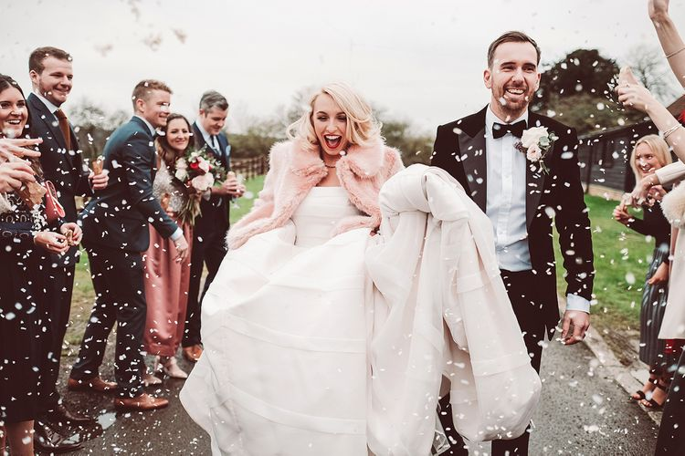 Confetti Moment | Bride in Organza Justin Alexander Gown & Blush Pink Faux Fur Coverup | Groom in Black Tie Suit | Blush Pink & Red, Christmas, Winter Wedding at Coltsfoot Country Retreat | Lemonade Pictures