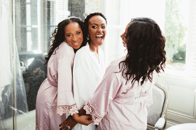 Bride and bridesmaids in white and pink getting ready robes