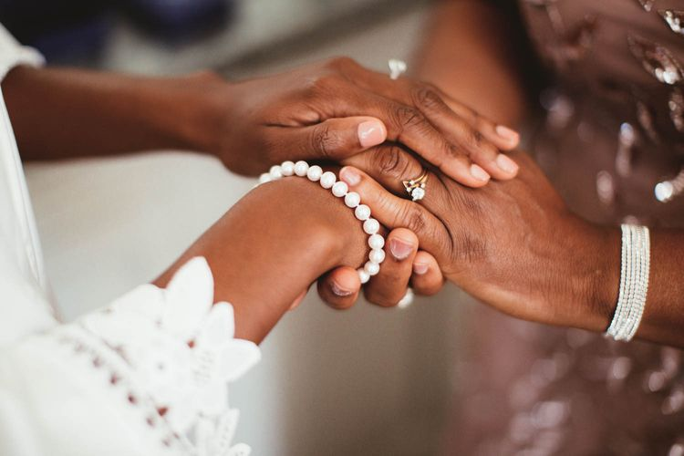 Bride and mother of the bride holding hands on the wedding morning
