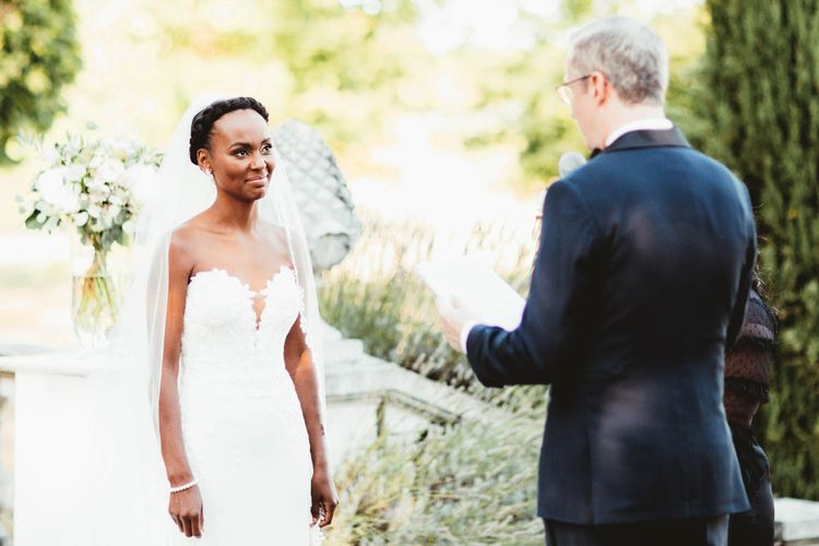 Bride in strapless Pronovias wedding dress and Groom in Tuxedo exchanging vows