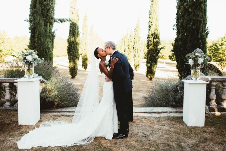 Bride and groom kissing at the altar at their Chateau La Durantie outdoor wedding ceremony