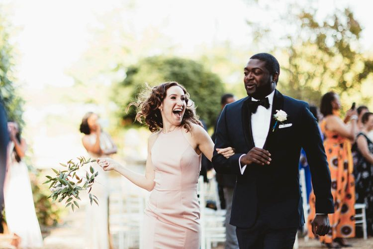 Groomsmen and bridesmaids in pink dresses walking up the aisle