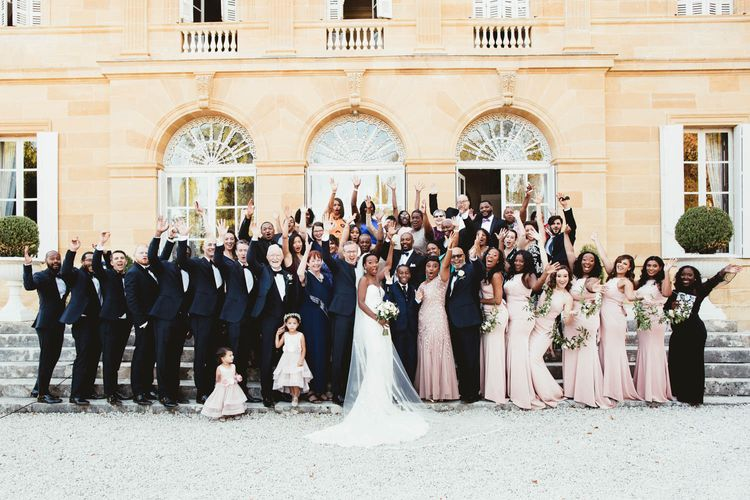 Group wedding guests portrait with pink bridesmaid dresses and tuxedos