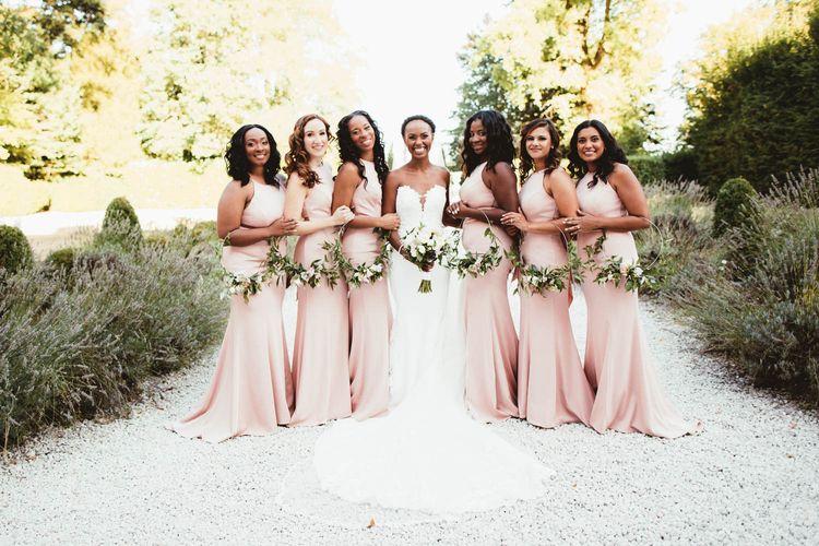 Bridal party portrait with pink bridesmaid dresses and Pronovias wedding dress